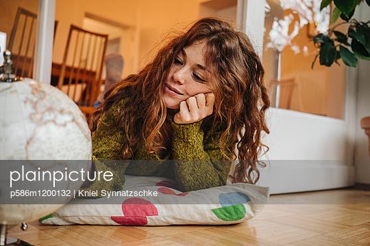 Junge Frau schaut auf einen Globus - p586m1200132 von Kniel Synnatzschke
