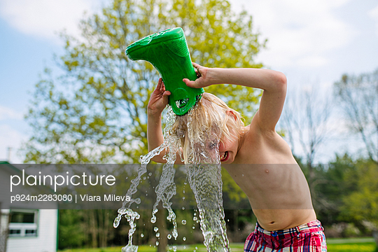 Canada, Kingston, Shirtless boy pouring water from rubber boot on head - p924m2283080 by Viara Mileva