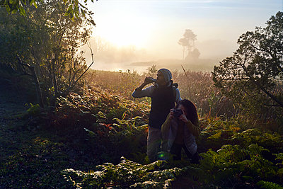 Curious young couple hiking with binoculars and camera in sunny woods - p1023m2212929 by Trevor Adeline