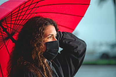 Portrait of a curly woman holding a red umbrella in Palma, Spain - p1166m2212828 by Cavan Images