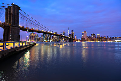 USA, New York, New York City, East River and Brooklyn Bridge at purple dawn with Manhattan skyline in background - p300m2199214 by Lorenzo Mattei