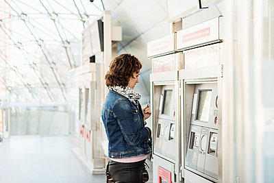 Side view of businesswoman looking at ticket machine in railway station - p426m1085315f by Kentaroo Tryman