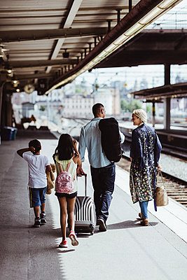 Man with luggage talking to family while walking at train station - p426m2146113 by Maskot