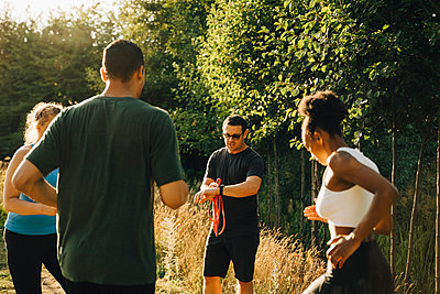 Fitness instructor training male and female athletes while exercising in park - p426m2270792 by Maskot