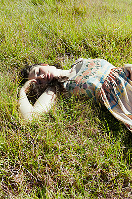 Girl resting in grass - p956m1044256 by Anna Quinn