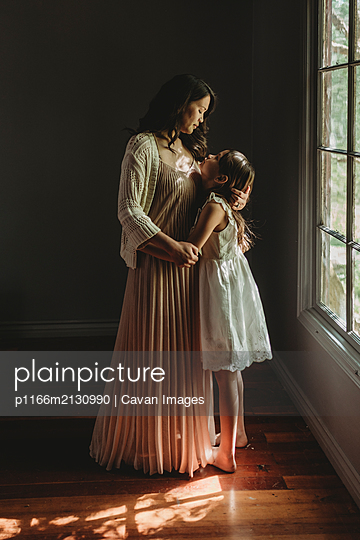 Mother and daughter embrace and looking at each other by window - p1166m2130990 by Cavan Images