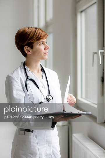 Ärztin mit Patientenunterlagen am Fenster - p1212m1123346 von harry + lidy
