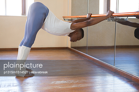 Ballerino stretching on a barre while practicing ballet dance - p1315m1514527 by Wavebreak