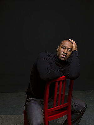 Portrait confident African American man straddling chair against black background - p1192m1403576 by Hero Images