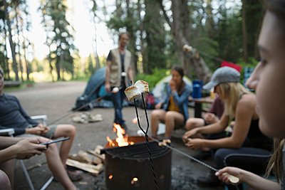 Teenage outdoor school students toasting marshmallows at campsite campfire - p1192m1490919 by Hero Images