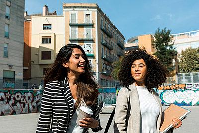 Barcelona Spain, friends walking in downtown Barcelona, friends young people spain urban city  - p300m2226831 von Valentina Barreto