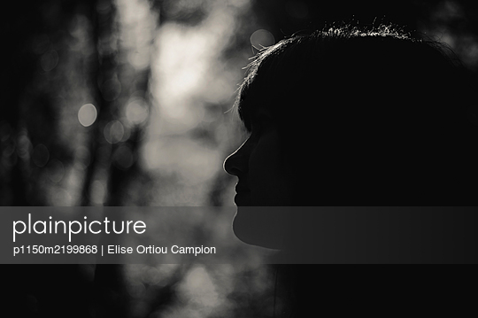 Profile of young woman against the light - p1150m2199868 by Elise Ortiou Campion