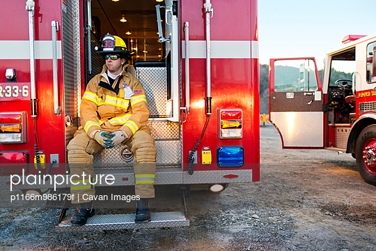 Fireman Seated on the Back of a Fire Engine