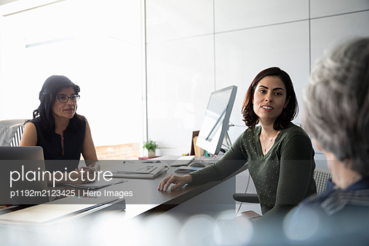 Businesswoman talking to clients in office - p1192m2123425 by Hero Images