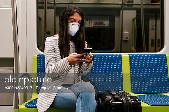 Female passenger using smart phone while sitting in metro train - p300m2240317 by Ezequiel Giménez