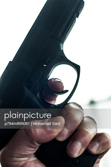 Man holding a gun  - p794m899081 by Mohamad Itani