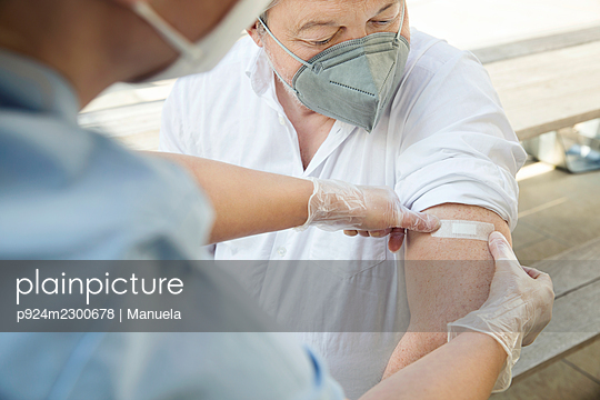Austria, Vienna, Close-up of nurse applying adhesive bandage on patients arm - p924m2300678 by Manuela