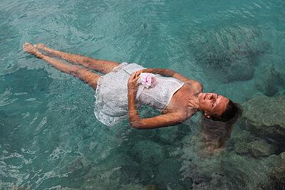 Frau im Kleid treibt auf Wasseroberfläche - p045m2037998 von Jasmin Sander