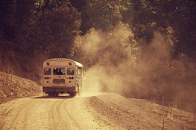 Bus driving on a dusty road - p1072m830393 by Joe Eitzen