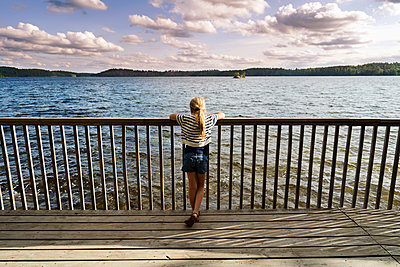 Rear view of girl standing on jetty by railing over lake and looking at view - p1166m1229476 by Cavan Images