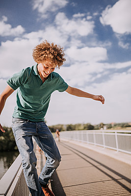 Young man on a bridge, portrait - p1267m2259696 by Jörg Meier