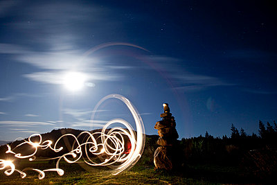 Rock cairn with light painting next to it and full moon in background in Idaho - p3436825f by Patrick Orton