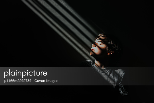 Young boy sitting in a patch of patterned light in a dark room. - p1166m2292739 by Cavan Images
