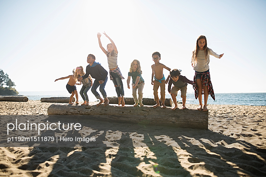 Exuberant boy and girl friends jumping off log on sunny ocean beach - p1192m1511879 by Hero Images