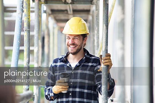Smiling construction worker holding container standing by scaffold at construction site - p300m2214127 by MiJo