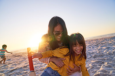 Happy mother and daughter hugging on sunny sunset beach - p1023m2200829 by Trevor Adeline