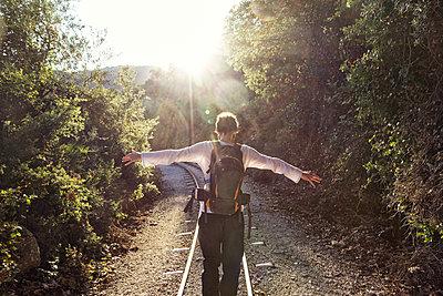 Greece, Pilion, Milies, back view of man with backpack balancing along rails of Narrow Gauge Railway - p300m1581131 von Maria Maar