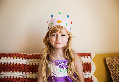 Portrait of girl wearing crown while sitting on bed at home - p1166m1097046f by Cavan Images