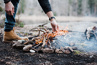 man putting logs on a handmade campfire outdoors in Sweden - p1166m2179457 by Cavan Images
