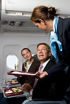 Business people on a plane being served meals and champagne - p3018289f by Halfdark
