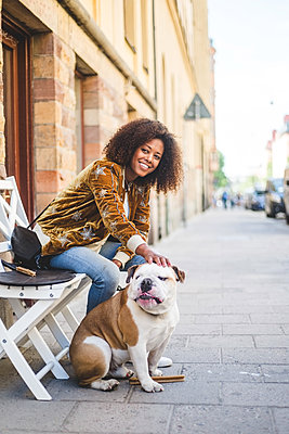 Smiling woman sitting with dog on sidewalk in city - p426m2046359 by Maskot