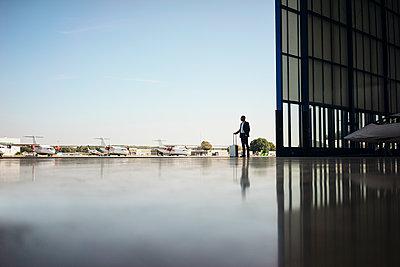 Businessman with rolling case on runway - p586m1208482 by Kniel Synnatzschke