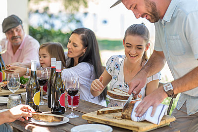 Man slicing bread at outdoor family lunch - p924m1493729 by Zero Creatives
