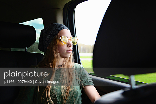 Beautiful tween girl with long blond hair and sunglasses in car. - p1166m2279440 by Cavan Images
