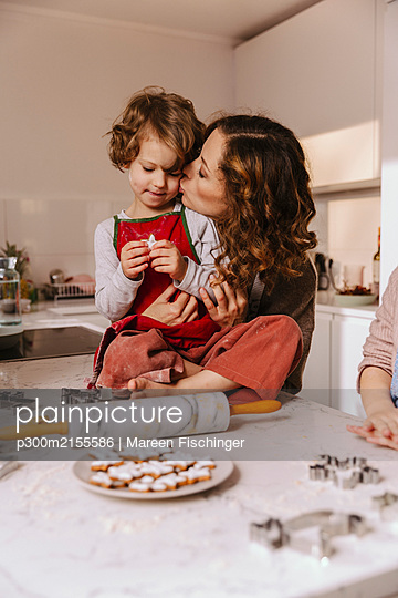 Mother kissing daughter in kitchen with Christmas cookies on counter - p300m2155586 by Mareen Fischinger