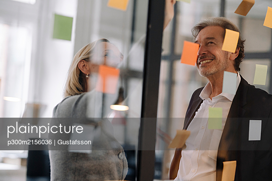 Happy businessman and businesswoman working on sticky notes at glass pane in office - p300m2156036 by Gustafsson