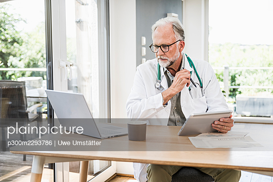 Male doctor using wireless technologies at desk - p300m2293786 by Uwe Umstätter