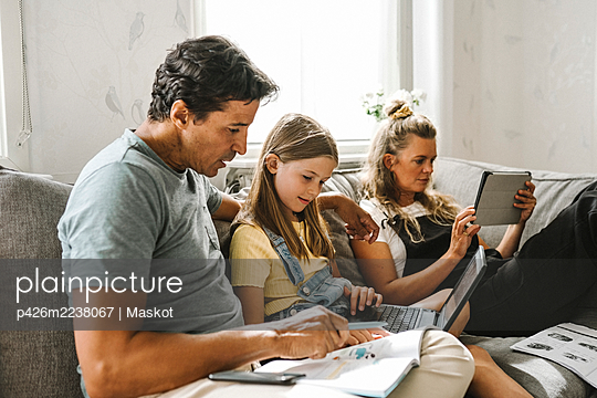 Father teaching daughter while mother sitting beside using digital tablet at home - p426m2238067 by Maskot