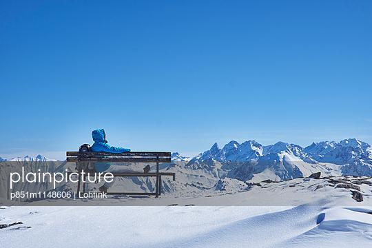 Frau auf einer Bank vor Winterlandschaft - p851m1148606 von Lohfink