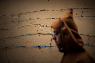 Strings on a wall and man walking  - p1007m2092404 by Tilby Vattard