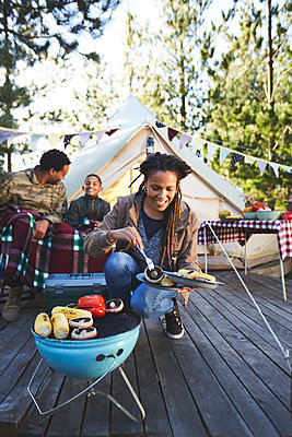Smiling woman cooking vegetables on campsite grill - p1023m2135998 by Trevor Adeline