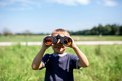 Playful boy looking through binoculars while standing on field during sunny day - p1166m1508383 by Cavan Images