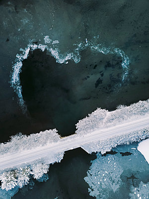 High angle view of snow covered bridge over frozen lake during winter - p1166m2001274 by Cavan Images