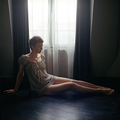 a woman by a window - p1610m2231172 by myriam tirler
