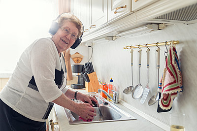 Portrait of senior woman listening music with headphones while washing up - p300m1417154 by Frank Röder