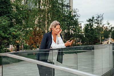 Mature businesswoman using smart phone while leaning on glass railing - p300m2293888 by Vasily Pindyurin
